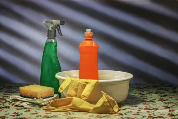 poisonous to dogs - a selection of cleaning products, including a sponge, bowl, yellow rubber gloves, and two bottles of detergent. One bottle has a screw cap, the other is a trigger spray bottle.