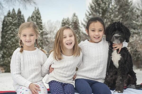 3 young girls sitting in the snow, one has her arm around a black scruffy dog.