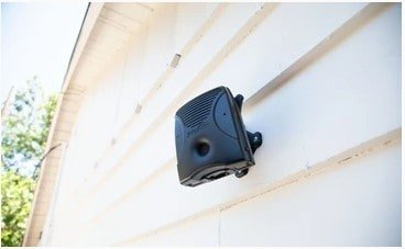 Dog barking device mounted to a wall on a house