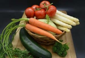What foods are good for dogs? an image of vegetables. Tomatoes, carrots, cucumbers, and some parsley