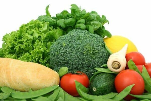 a diverse mix of vegetables with turnips, tomatoes, cucumbers, green peas, broccoli, lemons, some greens and basil