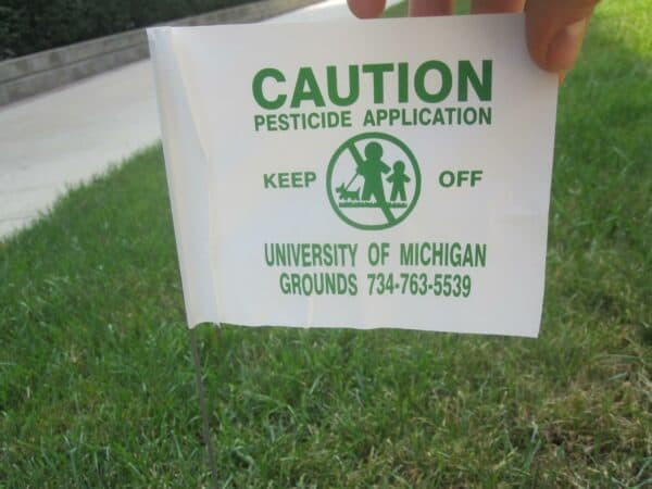 why do dogs eat grass then vomit? - a sign on the grass that says caution - pesticide was applied