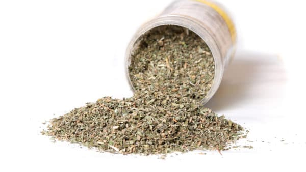 Dries catnip for dogs in a container that is spilling out onto a white desk.
