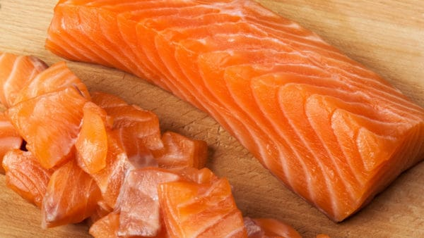 foods that are good for dogs - Image of a raw fish fillet alongside chopped fish
